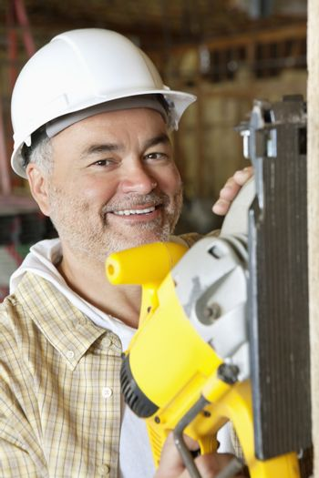 Portrait of a smiling male construction worker cutting wood with a circular saw