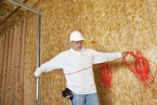 Mature male construction worker with an electrical wire