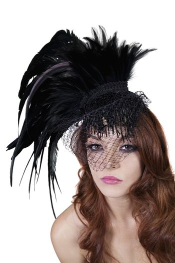 Portrait of young brunette wearing feathered veil over white background