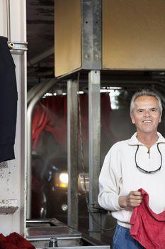 Half-length portrait of happy car wash owner