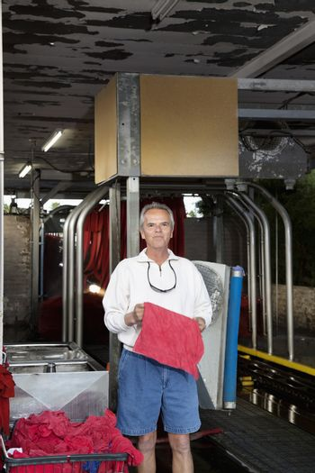 Portrait of a happy mature owner standing in car wash