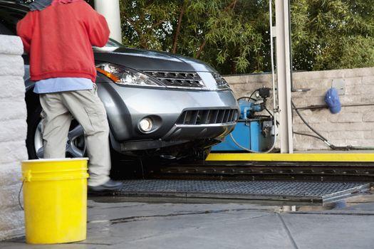 Car wash employee with vehicle on conveyor belt