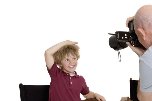 Senior photographer clicking school kid sitting on chair over white background