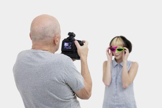 Senior photographer taking a photograph of fashion model during photo shoot