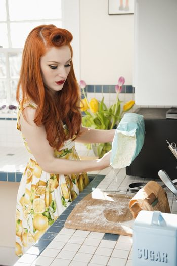 Young redheaded woman in preparation for baking