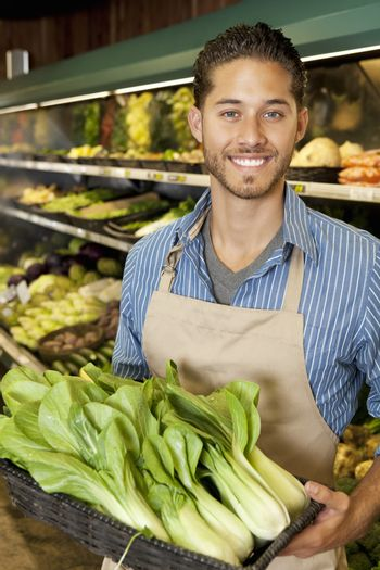 Portrait of handsome young sales clerk with bok choy in market