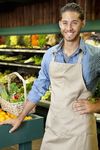 Handsome young sales clerk standing near stall in supermarket