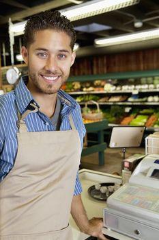 Portrait of handsome store employee standing near cash register in supermarket