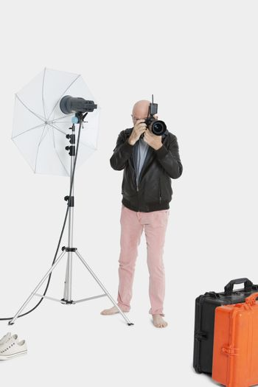 Senior photographer taking a photograph in studio