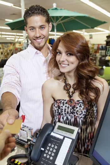 Portrait of a happy couple paying through credit card
