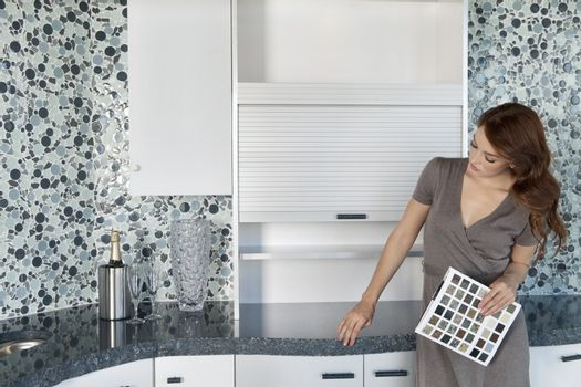 Beautiful young woman with color samples looking at contemporary kitchen cabinets