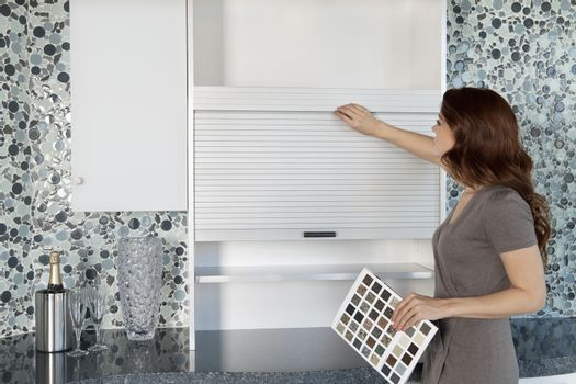 Young woman looking at cabinets in contemporary kitchen while holding color samples