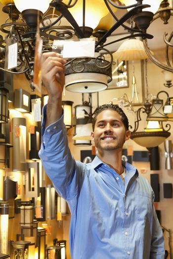 Happy young man looking at price tag of chandelier in lights store