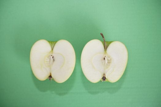 Sliced green apple over green background
