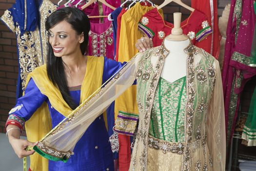 Indian female dressmaker measuring traditional outfit at design studio