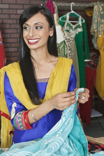 Indian female dressmaker looking away while holding sari
