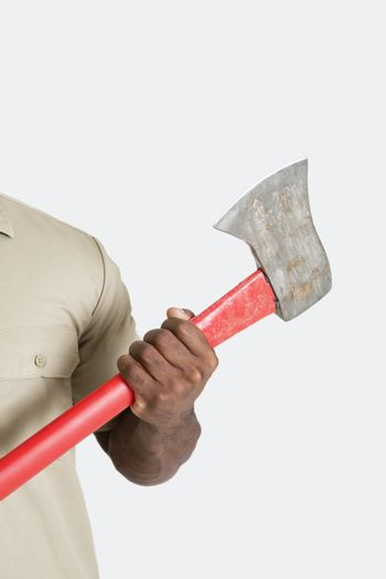 Male hand holding axe over gray background