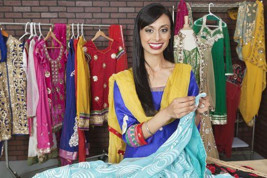 Portrait of an Indian female dressmaker working at design studio
