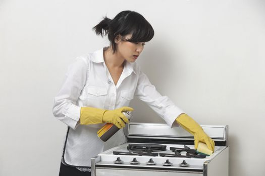 Young housemaid cleaning stove against gray background