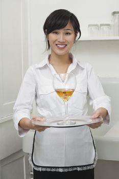 Portrait of female housekeeper serving wine in goblet