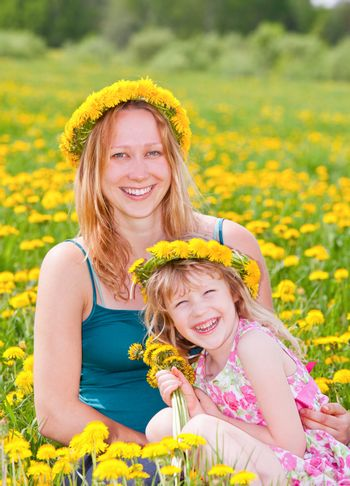 Young pregnant  woman with cute little girl enjoying a summer day outdoors