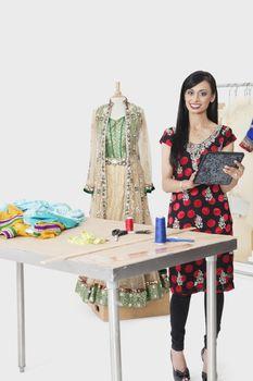 Portrait of Indian female dressmaker at design studio