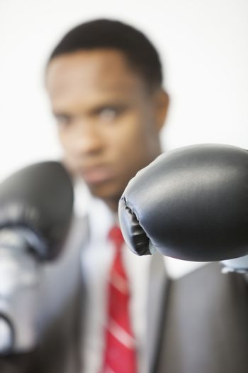 Businessman wearing boxing gloves with focus on gloves