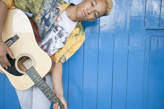 Portrait of a teenage boy playing guitar against wood paneled wall