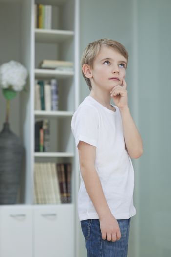 Little boy lost in thoughts at home