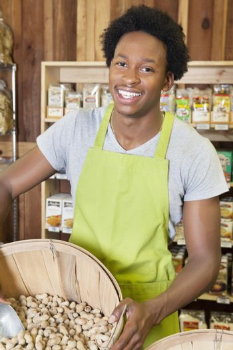 Male African American store clerk holding basket of peanuts