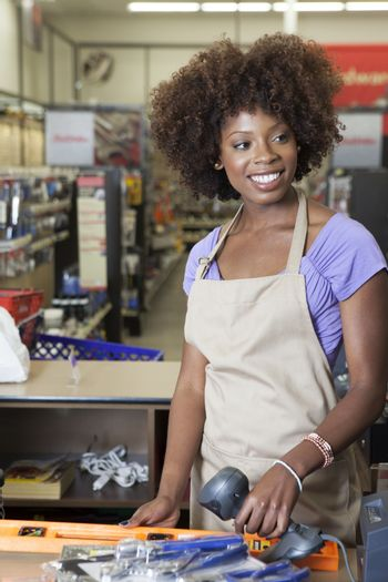 Portrait of an African American female store clerk standing at checkout counter scanning item