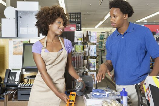 Female store clerk looking at customer while scanning product at super market