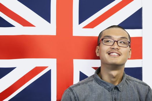 Contemplated man looking away while against British flag