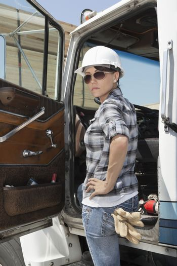 Confident female industrial worker standing by vehicle door with hand on hip
