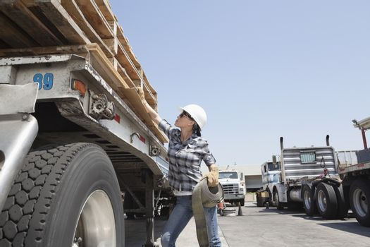 Female industrial worker strapping down wooden planks on logging truck