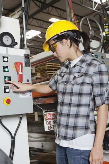 Female industrial worker operating manufacturing machine at factory