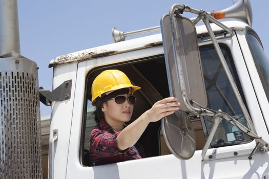 Asian female industrial worker adjusting mirror while sitting in logging truck