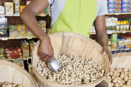 Mid section of store clerk with basket of peanuts
