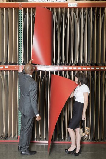 Multiethnic business colleagues selecting thin red veneer sheets