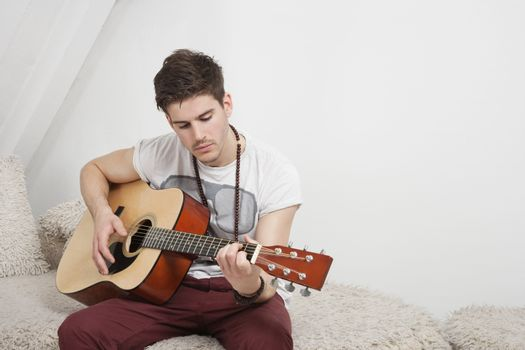 Young Caucasian man playing guitar while sitting on fur sofa
