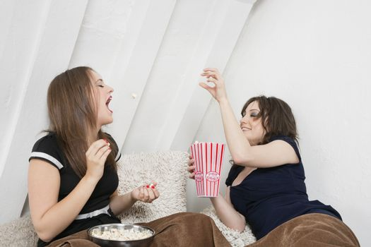 Playful young female tossing popcorn into friend's mouth in bed