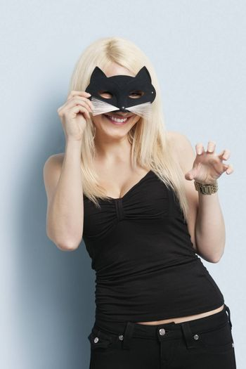 Portrait of young woman wearing a cat mask over light blue background