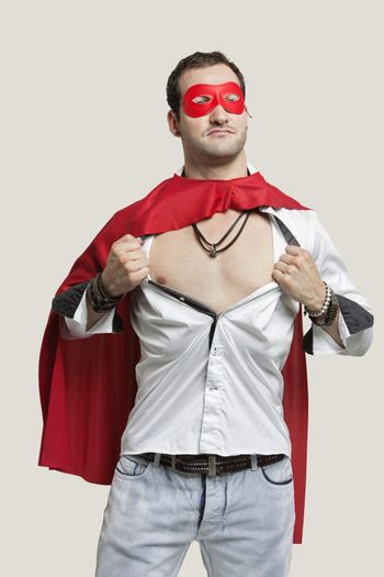 Young man in superhero costume standing against gray background