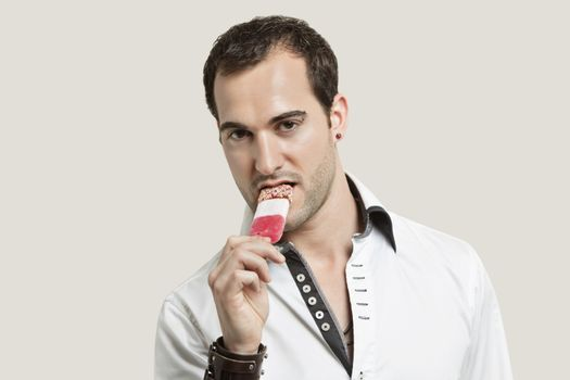 Portrait of young man eating ice cream candy against gray background
