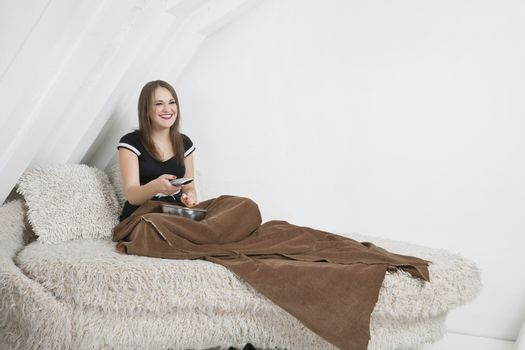 Smiling young woman in bed holding remote control