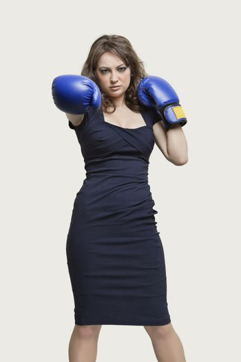 Portrait of a young woman wearing blue boxing gloves against gray background