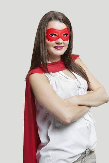 Portrait of a young woman in super hero costume over gray background