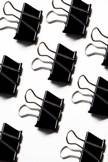 Group of binder clips over white background