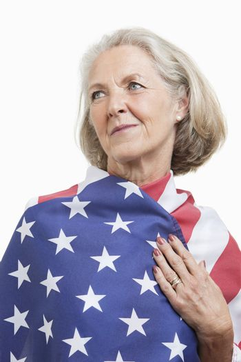 Senior woman wrapped in American flag against white background