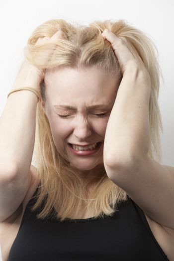 Frustrated young Caucasian woman with hands in hair against white background
